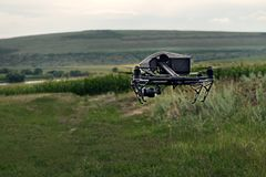 The concept people and agriculture - black drone with digital camera flying in sky over field on sunset. stock image