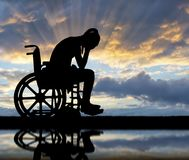 Concept of people with disabilities experiencing grief and sadness. Silhouette of a sad disabled woman in a wheelchair by the river with her reflection. The royalty free stock photography