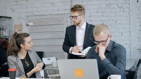 Man using computer while two manager discussing project. Concept of people team work in corporation. Confident and professional employee using laptop computer stock video footage