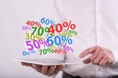 Concept of percent discount. Percent discount concept above a tablet held by a man in background Royalty Free Stock Images