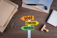 Concept perdu, confus et perplexe Poteau indicateur de papier sur un bureau en bois Images stock