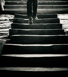 Concept: a person is going away by the stairs to the outside. Image in monochrome tones Royalty Free Stock Images