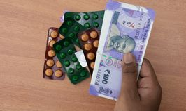 Concept of the person`s hands buying Pills or tablets with Indian currency.  stock images