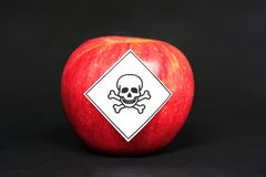 Concept of pesticide residues in agricultural food products dangerous to humans, showing a red apple with poison symbol royalty free stock photos