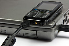 Concept phone connected to laptop via usb cable Stock Images