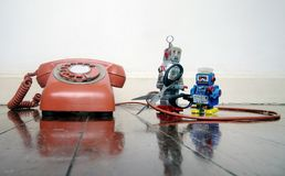 Concept phone line being cut of with retro robots. On a wooden floor royalty free stock image