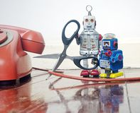 Concept phone line being cut of with retro robots. On a wooden floor royalty free stock images