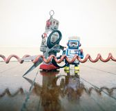 Concept phone line being cut of with retro robots. On a wooden floor stock images