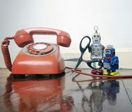 Concept phone line being cut of with retro robots. On a wooden floor royalty free stock photography