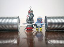 Concept phone line being cut of with retro robots. On a wooden floor stock photos
