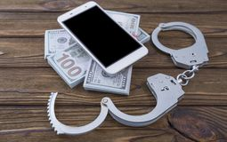 Smartphone money handcuffs on a tree background. Concept phone scammers. Smartphone money handcuffs on a tree background. Crime fraud punishment accession Stock Image