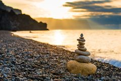 Concept photo balance at dawn - close-up of a pyramid of white stones. On a pebble beach royalty free stock image
