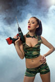 Concept photo. Beddable woman armed with drill Stock Photography