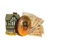 Bitcoin cryptocurrency finance. Concept photo of bitcoin and cash set against a cottage home ideal for mortgages finances trading etc Royalty Free Stock Image