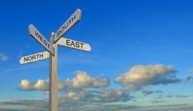Blue sky clouds sign post arrows direction north south east west. Concept photo of blue sky clouds with a sign post with direction arrows compass points stock photos