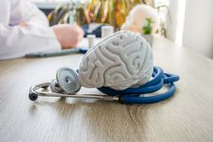 Concept photo of diagnosis and treatment of brain nervous. In foreground is model of brain near stethoscope on table in background. Blurred silhouette doctor at royalty free stock photography