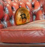Gold bitcoin cryptocurrency lost down sofa armchair royalty free stock photo