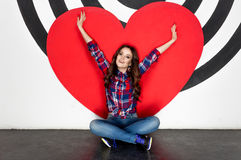 Concept photo of happy woman sitting on floor with big red heart Stock Photography