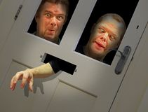Mad faces peering through door Stock Image