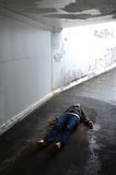 Concept Photo - Murder. Crime scene concept photo of a murder victim woman lying dead on the ground of a tunnel stock photo