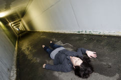 Concept Photo - Murder. Crime scene concept photo of a murder victim woman lying dead on the ground of a tunnel royalty free stock image