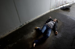 Concept Photo - Murder. Crime scene concept photo of a murder victim woman lying dead on the ground of a tunnel royalty free stock photo