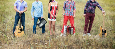 Concept photo of music band with guitars, microphone and accordion standing outdoors Stock Photo