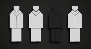 Concept photo showing isolation. Concept photo of a paper black man, that seems invisible on a black background among paper white figures Stock Photography