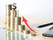 Concept photo showing value increase of dollar. tower made with coins stock images