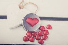 Some red candy hearts on a white wood box background. A concept photo with a some red hearts on a white wood box background Royalty Free Stock Photos