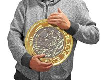 Holding gold british pound coin in arms. Concept photo of someone holding a british gold one pound coin ideal for savings banking economy etc royalty free stock images