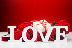 Concept photo of Valentine Day background. Rose, rings and gift Stock Image