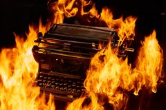Concept shot of antique manual typewriter with paper burning on black background, selective focus. Concept picture of antique manual typewriter with paper Stock Image
