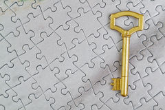 Concept picture golden key to the puzzle. Royalty Free Stock Photo