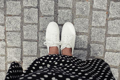Concept picture of legs walking, Selfie of feet in white sneaker on rock pavement background, top view. Royalty Free Stock Image