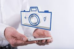 Concept of pictures sharing. Pictures sharing concept above a smartphone held by hands Stock Images