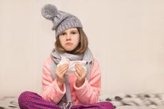 Little girl sneezes on white background with napkin, get cold outside. stock image
