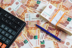 The concept of planning income and expenses: calculator and ball-point pen and a pack of half a million Russian rubles in the bank stock photos