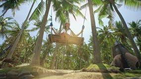 Concept: plezier, geluk en vrijheid Vrijheidsvrouw reis concept Meisje die pret hebben die op een kabel bij tropisch slingeren stock videobeelden
