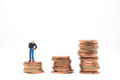 Concept of poor man saving. Poor man searching coin in pocket standing on coin stack royalty free stock photos