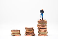 Concept of poor man saving. Poor man searching coin in pocket standing on coin stack stock image