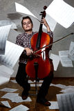 Concept portrait of a cellist. Concept portrait of a young cellist with flying paper stock image