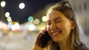 Concept portrait of youthful attractive beatiful long-haired girl speaks on the phone and laughs blurred night lights stock video footage