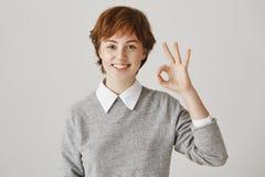 Concept positif d'émotions Fille rousse de garçon charismatique avec la coupe de cheveux courte et l'équipement élégant montrant  photo stock