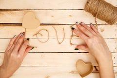 Concept pour des histoires d'amour et pour la Saint-Valentin Les mains femelles font des boîtes sous forme de coeur et d'inscript photos stock