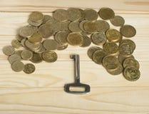 Concept pour les immobiliers ou louer la clé de propriété et pièces de monnaie sur le fond en bois photographie stock libre de droits