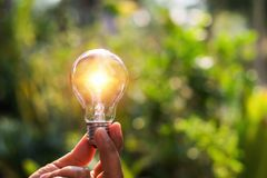 Concept power energy of solar in nature. hand holding light bulb. With sunset royalty free stock photography