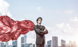 Concept of power and sucess with businessman superhero in big ci. Young confident businessman wearing red cape against modern city background royalty free stock images
