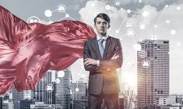 Concept of power and sucess with businessman superhero in big ci. Young confident businessman wearing red cape against modern city background stock image