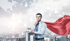 Concept of power and sucess with businessman superhero in big ci. Young pensive businessman wearing red cape against modern city background stock image